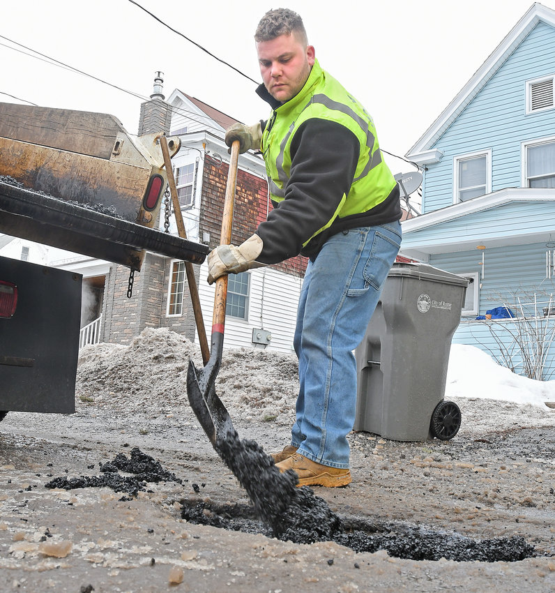 POTHOLE SEASON — DPW is taking advantage of the mild weather, as city worker Andrew DeBlasiis fills in a pothole on William Street with cold patch this morning. Residents can report potholes and other non-emergency issues to City Hall by downloading the RomeNY 311 app, available on iOS and Android devices, and following the onscreen instructions. This winter — with its fluctuating temperatures and mixed precipitation — has been ideal for  spawning potholes, which are often created when the precipitation leaks through cracks in streets and roadways and pools under the pavement and then expands as it freezes when temperatures drop.