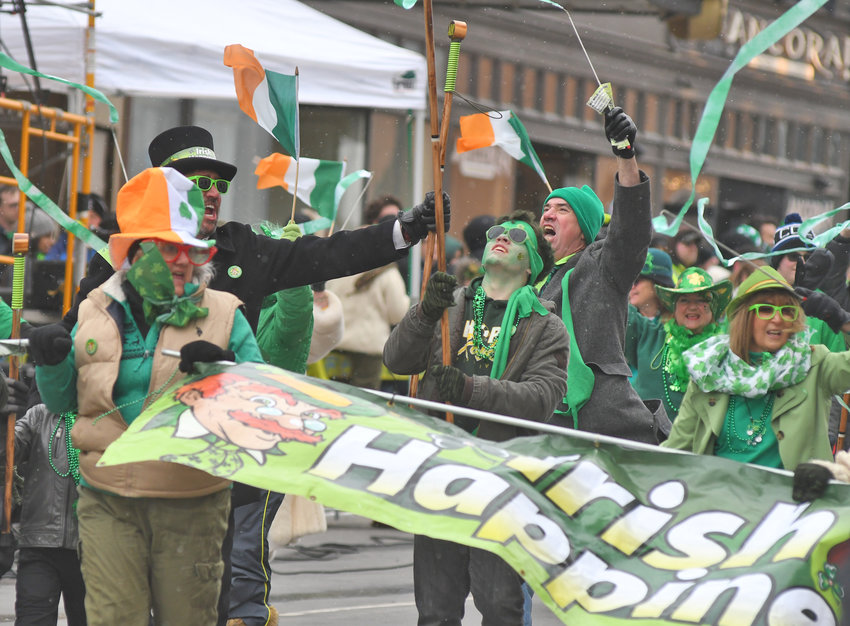 """READY FOR THE SHENANIGANS —A few snowflakes and blustery winds fail to dampen the enthusiasm of """"The Corrigan Thats Me"""" marchers during the St. Patrick's Day parade on Genesee Street in Utica on Saturday. Dozens of organizations participated in the annual event with thousands of spectators braving the elements to enjoy the revelry."""