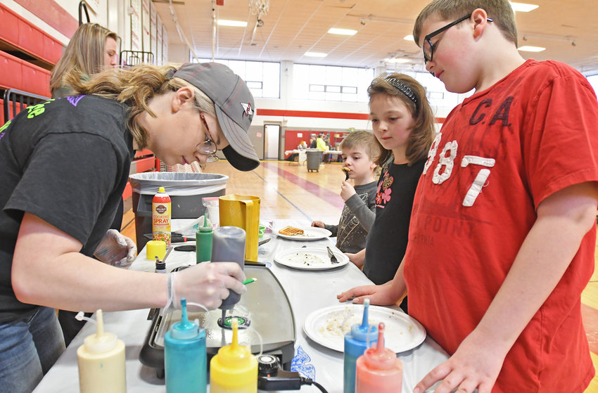 PANCAKE ART — Vernon-Verona-Sherrill Future Farmers of America (FFA) President Gabby Adams, left, makes an artistic pancake with colors under the watchful eyes of Ash Parker and his twin sister Willow Parker and Reed Gibson, 6, at the pancake breakfast this morning during their annual Maple Weekend at VVS High School. VVS FFA Vice President Danann Lohr is in the background on the left. This is the first of two weekends of events.