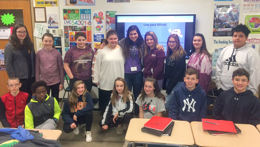 SPREADING THE MESSAGE — Julia Petreikis, standing at center, gathers with seventh-graders in Vernon-Verona-Sherrill Middle School health teacher Cheryl Friske's class on Tuesday. Petreikis was a guest speaker to help raise students' awareness about epilepsy.