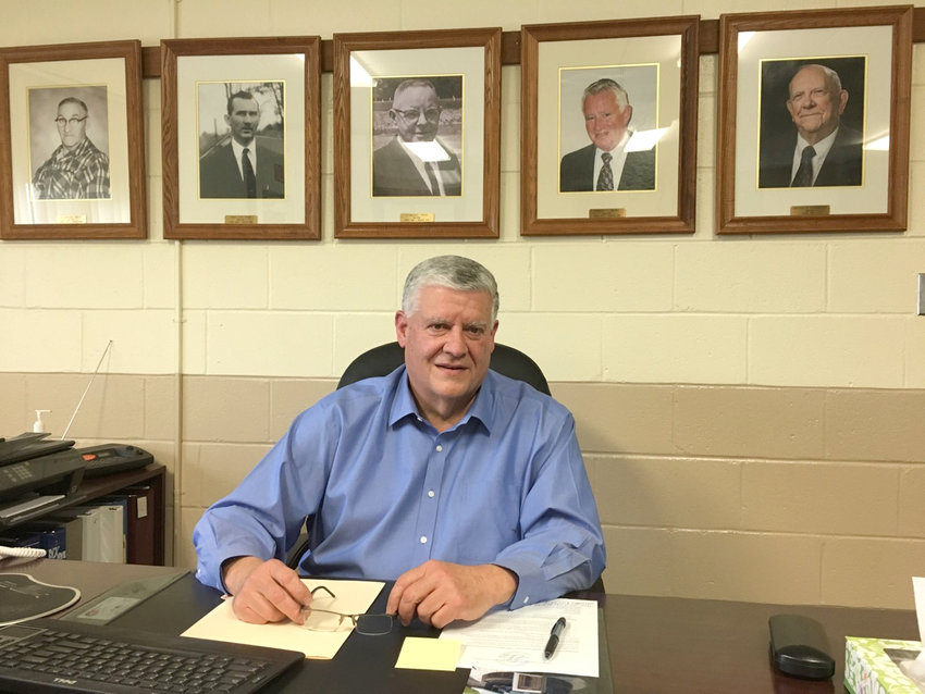 NEW MAYOR — Clifford O'Connor sits at his new desk at the Oriskany Village Offices on Utica Street. O'Connor, who previously served as village trustee, recently took the helm as mayor, replacing long-time Mayor Donald F. Rothdiener, who is now officially retired. Behind O'Connor are photos of the village's former mayors, including Rothdiener.