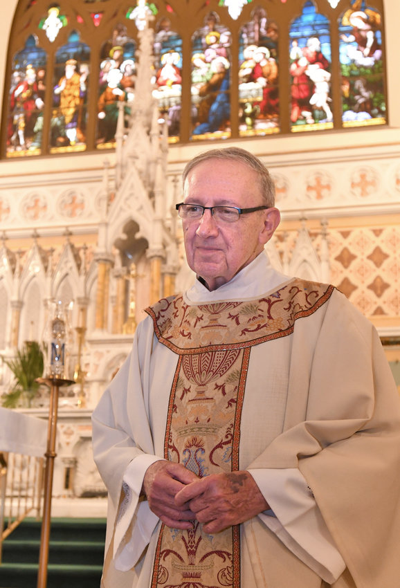 53 YEARS OF SERVICE — Father Philip Hearn of St. Peter's/St. Mary's Church stands at the St. Peter's altar on Monday. Father Hearn is retiring from the priesthood, effective July 1, after 53 years of service, and will relocate to his hometown of Syracuse to assist at parishes there.
