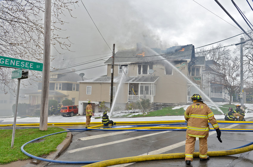 HOSE ATTACK — Multiple hose lines blast water at the roof and second floor of 132 Genesee St. in New Hartford on Saturday. Officials said the fire is believed to have started on the second floor. Flames took more than an hour to get under control. See story, page 2.