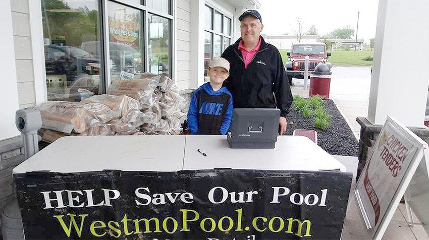 RAISING MONEY — Westmoreland Summer Activities Association president Scott Tarkowski with his son Ryan selling raffle tickets to raise money for the pool.