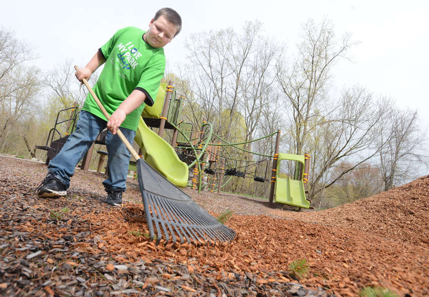 "READYING THE PLAYGROUND — Joshua Stevens, 11, spreads wood chips on a playground area at Delta Lake State Park on Saturday during the annual ""I Love My Park Day"" cleanup and beautification event. Several dozen people were at Delta park for the event, part of similar activities held Saturday at more than 140 state parks, historic sites and public lands across the state."