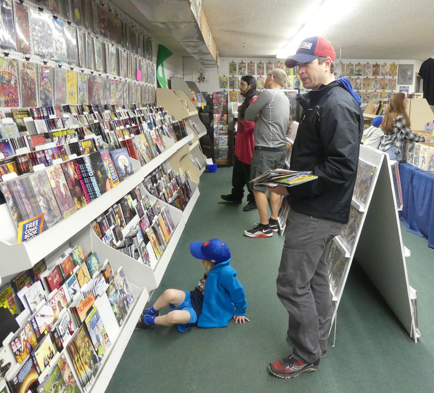 NATIONAL COMIC BOOK DAY — Nolan Rosefeld, 5, a Spiderman fan, sits and waits for dad Josh Rosefeld, both of Whitesboro, to make his comic book choice at Ravenswood Comics in New Hartford during the annual free comic book day Saturday, May 4 which also happened to be May the Fourth Be With You day.
