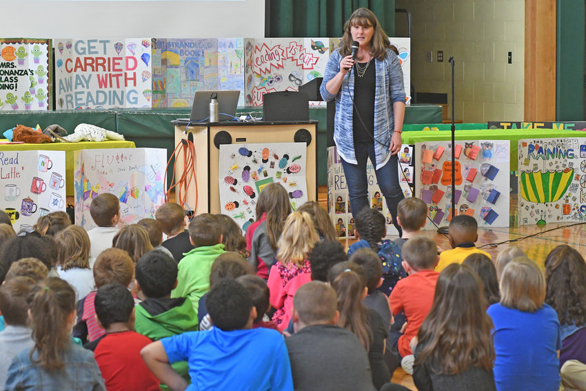 """AUTHOR ON THE SCENE — Students at Gansevoort Elementary School, 758 W. Liberty St., listen intently to author Kate Messner discuss her book """"Marty McGuire."""" Messner, from just south of Plattsburg, and the students were discussing the chapter book about a girl who would rather spend recess catching frogs than playing dress-up and the unintended consequences from her being cast as a princess in the class play."""