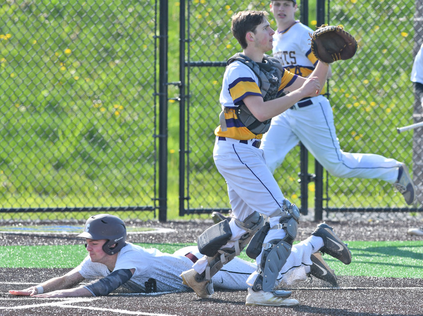 INSIDE THE PARK HOMER — Holland Patent catcher Jake Beer awaits a throw home as Clinton's Tanner Deveans slides home safely on an inside-the-park home run on Friday, May 17. The Warriors, who are 7-7 overall, lost 9-8.