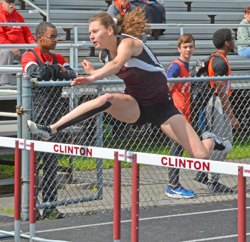 ATTACK MODE —Clinton junior Roxee Hughes clears a hurdle with her lead leg winning the 100-meter hurdle event with a time of 16.48 seconds at Clinton Central School's Junkyard Relays on Saturday, May 18. Clinton went on to win the event with a total of 166 points.