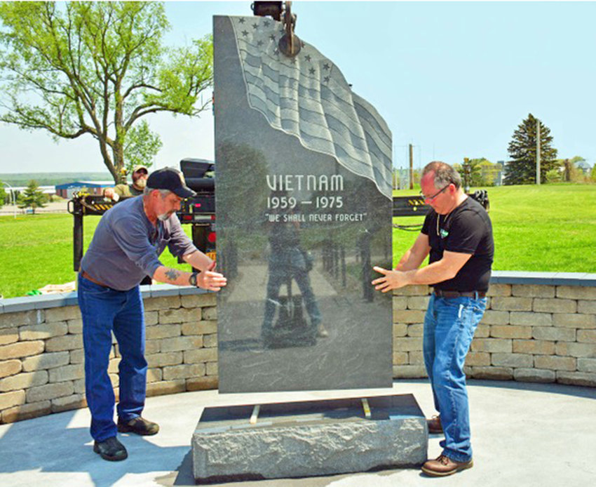 FINAL PREPARATIONS — The final stone for Rome's Vietnam Veterans Memorial at Griffiss Park was recently placed. Helping to guide the stone into place are Rick Falcone, Vietnam Memorial Committee president, left, and Greg Ellinger Jr., committee associate member. The crane operator and provider of the stone are Ron and Jody Hunt of Kellogg Memorial in Rome. At the rear is photographer Michael Richardson.  The Rome Vietnam Veterans Memorial will be dedicated during a ceremony at 2 p.m. Memorial Day, Monday, May 27.