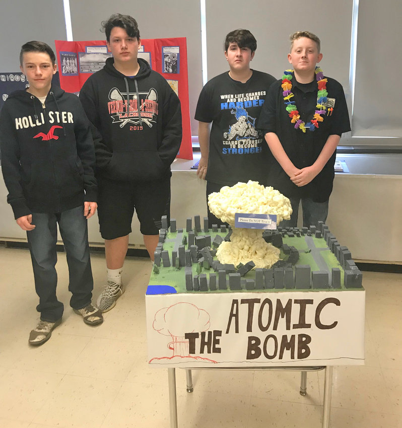 MARKING MOMENT IN HISTORY— A display marking the atomic bomb usage that helped lead to the end of the World War II was part of a World War II museum display that was hosted by a Vernon-Verona-Sherrill Middle School team. Among participants, from left: Traie Wickham, Vincent Laribee, Jack Bailey and Joseph Ingalls.