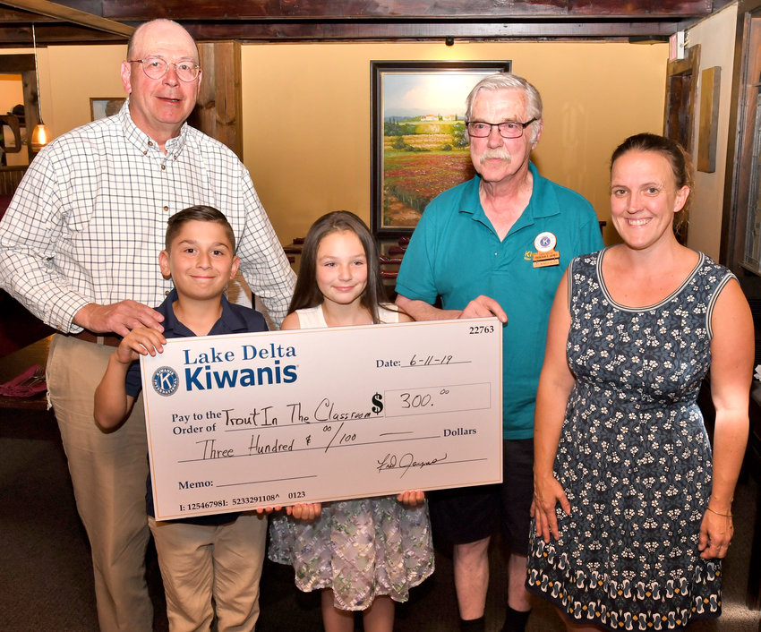 """KIWANIS SUPPORTS TROUT PROGRAM — The Lake Delta Kiwanis Club presented a $300 check for its continued support of the """"Trout in the Classroom"""" program which is in conjunction with the Trout Unlimited organization. From left: Gary Bartell, Trout Unlimited regional instructor; Carlo D'Alessandro and Leah Lyness, students at Stokes Elementary School where fourth-graders recently released about 200 brook trout at Pixley Falls; Fred Jaynes, president of Lake Delta Kiwanis Club; Tanya Erway, fourth-grade teacher at Stokes."""