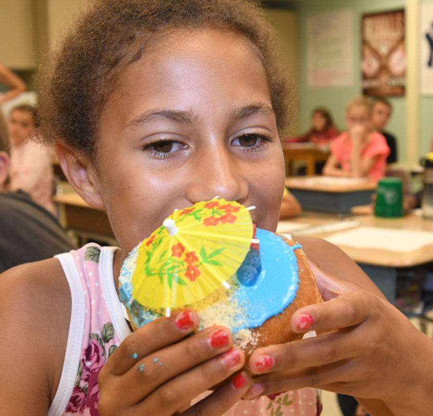 """A CREATIVE TASTE — Gansevoort Elementary School fourth-grader Myiah Fowler takes the first bite of the """"Beach Donut"""" that was made by Dippin Donuts based on Fowler's suggestion of it as a new flavor in a fourth-grade persuasive essay contest. Her essay was chosen as the contest winner, and students got to sample a batch of the """"Beach Donut"""" Thursday at Gansevoort."""
