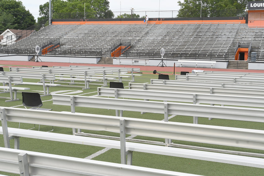 GETTING READY FOR SATURDAY — Rome school district employee Tom Baker, in the background at center in the top row at Rome Free Academy Stadium, puts the finishing touches on some painting Thursday morning as part of preparations for RFA's graduation ceremony Saturday for its Class of 2019. Seats for the graduating students have been placed on the stadium field.