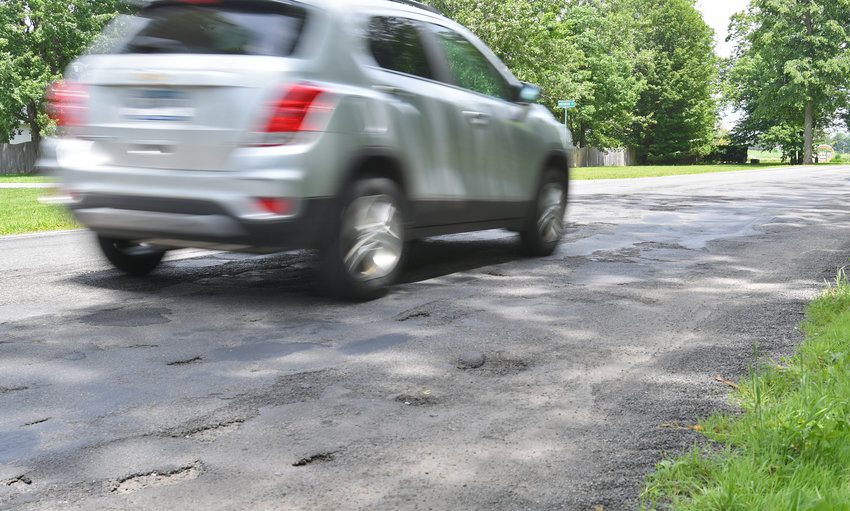 BUMPING ALONG —A motorist drives along Potter Road, which is pitted with potholes and considered among dozens of city streets most in need of repair, on Thursday afternoon. The city has finalized its list of 50 streets to be resurfaced this summer with work expected to begin on Monday, July 8 with a tentative completion date of Sept. 27.