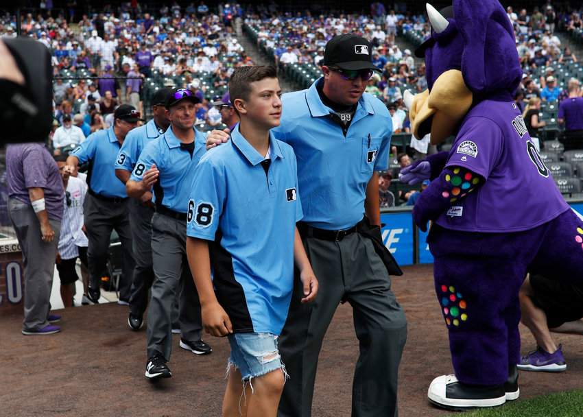 CENTER OF ATTENTION — Thirteen-year-old Josh Cordova, left, of Denver, heads on the diamond with home plate umpire Cory Blaser before the Colorado Rockies host the Los Angeles Dodgers in the first inning of a baseball game on June 30 in Denver. The young man was officiating a youth baseball game when a brawl broke out among adults in the nearby suburb of Lakewood, Colo.