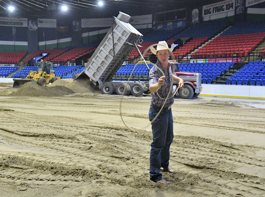 LASSO LESSON —Dalton Morris of Kansas City practices his moves while crews put down dirt in the Utica Aud Tuesday. Morris will be part of the Utica Stampede rodeo there Thursday and Friday, an American Professional Rodeo Association event.