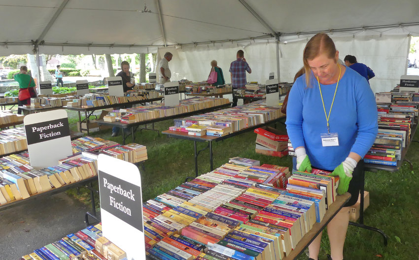 """RECORD SALES — Rebecca Hewitt, a Friends of the Kirkland Town Library volunteer, says the Friends Annual Book Sale on Friday, July 12 at the Clinton Village Green was """"on track for record sales"""" this year with 31/2 trucks full of donated books."""
