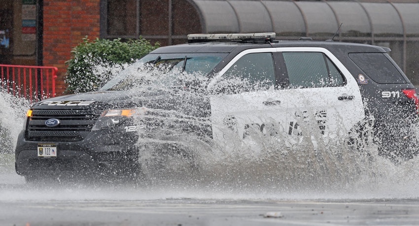 INNUNDATED — An early afternoon downpour led to several flooded intersections in Rome today, including this one at the intersection of Erie Boulevard West and South Madison Street. Above, a Rome Police Department cruiser tries to navigate through high water in front of Wendy's Restaurant.  According to reports, additional intersections, including Turin Road and North Madison Street and West Chestnut Street and North Madison Street had also experienced flooding.