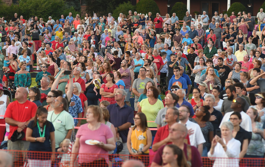 HONORING THE ANTHEM — An audience that stretched across the lawn at Fort Stanwix National Monument stands during the playing of the National Anthem at the Honor America Days Concert by Symphoria Symphony on Saturday night.