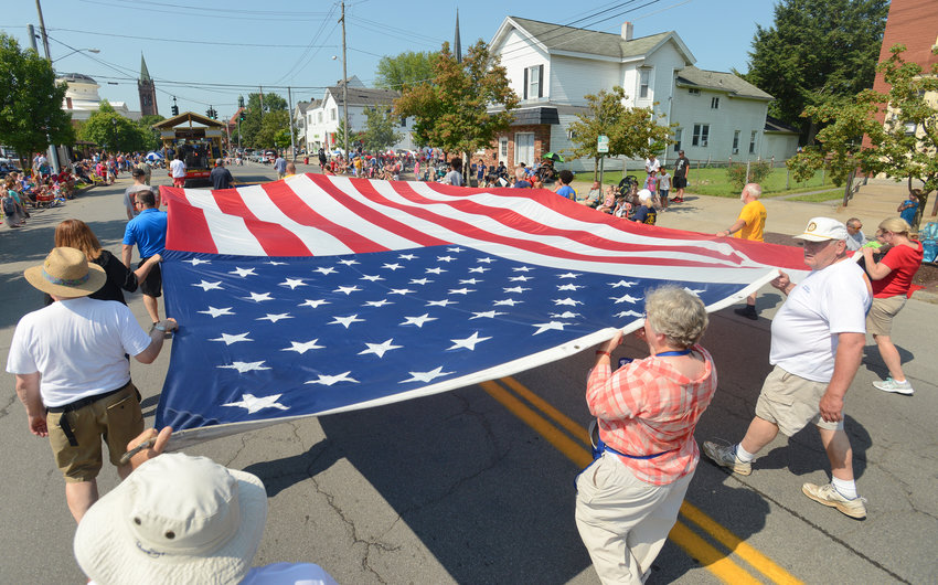 RED, WHITE AND BLUE — Members of the Rome Rotary Club march with a large flag on North James Street Saturday morning during the Honor America Days Celebrations.