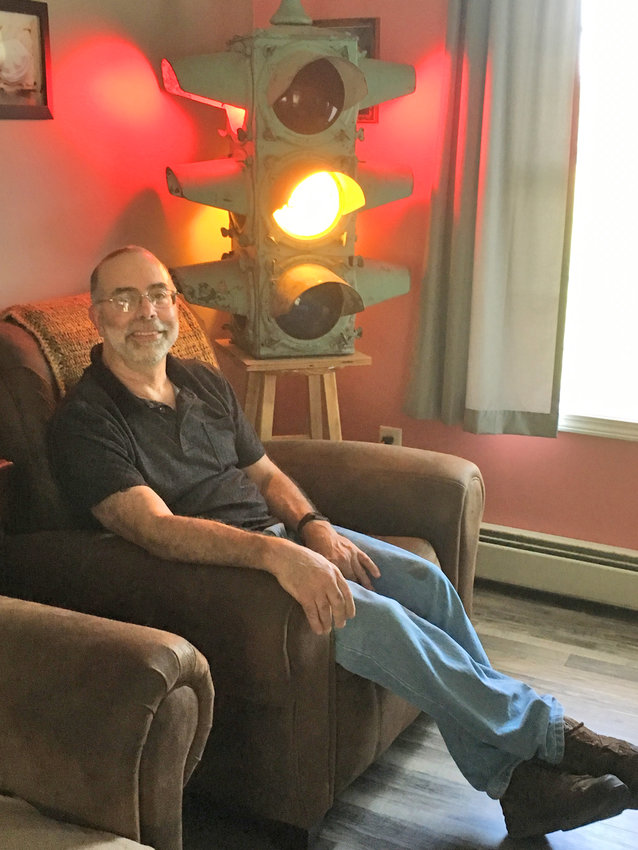 HE LIKES LIGHTS — Tony Taurisano, of Lower Lawrence Street in Westmoreland, has been an avid collector of street lights for the last five years. Some can even be found in his living room.