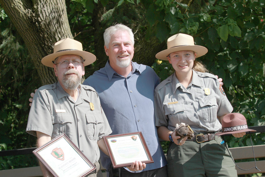 BEARING GIFTS — Rosamond Gifford Zoo's Director Ted Fox is flanked by Fort Stanwix National Monument rangers Dan Amsted and Arielle Goellner. Both rangers brought gifts for one of the zoo's newest residents, a baby bison named Madison.