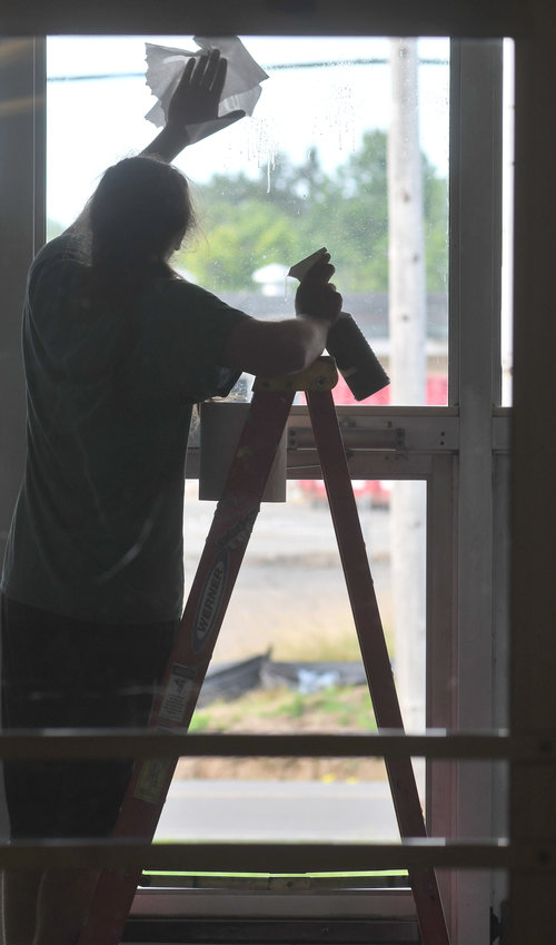 SCHOOL SILHOUETTE — Kegan Marchione, a Rome Catholic School custodian, cleans a window in preparation for the new school year.