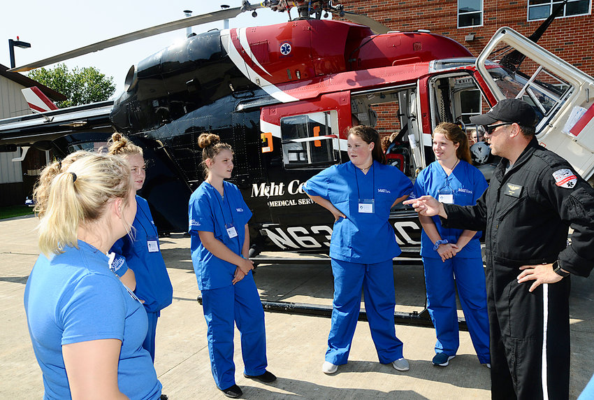 AN INSIDE LOOK — Sean Byard, right, a pilot for Mercy Flight Central, explains the inner workings of a rescue helicopter to students from the Medical Academy of Science and Health (M.A.S.H.) Camp, at Rome Memorial Hospital. 21 students from 12 different schools spent three days at the hospital learning about the wide array of healthcare careers available to interested students.