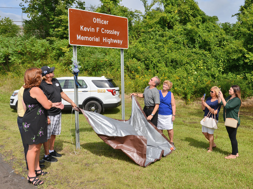 The Crossley family unveil the sign dedicated Kevin F. Crossley in Whitesboro Monday morning.