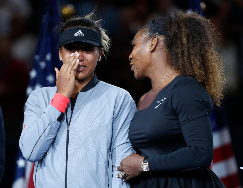 TEARFUL FINALE — In this Sept. 8, 2018 file photo, champion Naomi Osaka, left, wipes away tears as she talks with Serena Williams following the U.S. Open title match in New York.