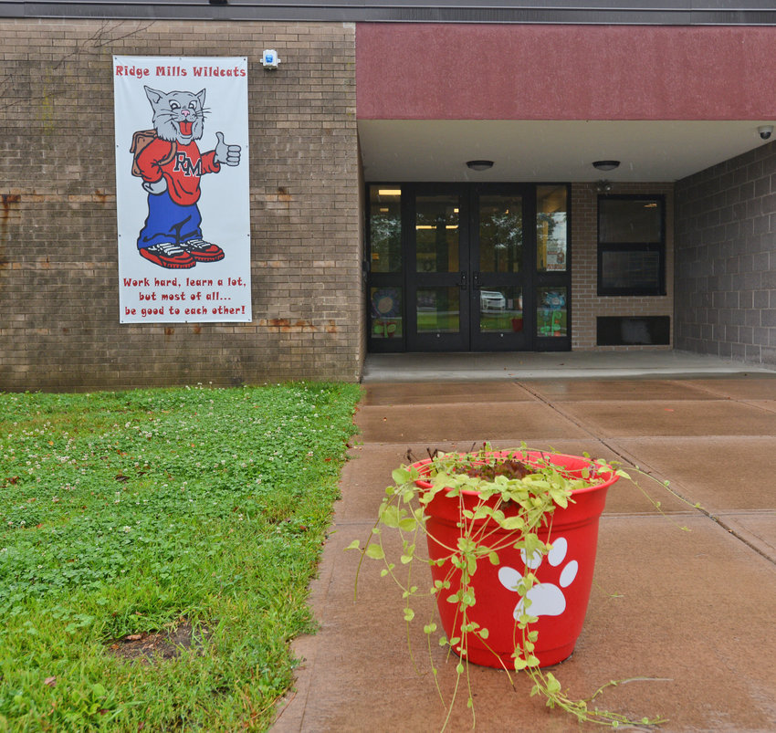 COME ON IN —A poster of the Ridge Mills Elementary School mascot greets visitors to the school's main entrance on Wednesday. A parent has cited concerns over class sizes, and questioned how many students are attending the school through transfer requests. Superintendent Peter C. Blake said class sizes at the school are consistent with others across the district and said the administration is following district policy regarding transfers at the building as well as the others throughout the district.