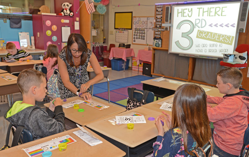 third grade teacher Mercedes Mills and some of her students as they work with play-dough just minutes in to the start of their first day of school.