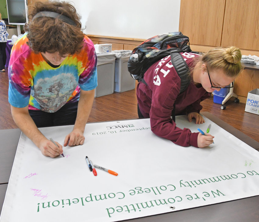 "VOWING TO GRADUATE — Isaiah Geer, left, from Holland Patent, and Shelby Kilts, from Canastota, both students at Mohawk Valley Community College sign their names, joining hundreds of other students on Tuesday vowing that ""We're committed to community college completion!"" during an event at MVCC's Rome Campus. Although the college's fall semester has just begun, advisers and other staff are available all year long to assist students toward the  goal of graduation, MVCC officials say."