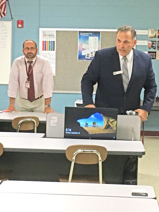 NEW TECHNOLOGY — Clinton Central School Superintendent Stephen L. Grimm, right, joined by Assistant Superintendent for Business Joseph Barretta, removes a computer monitor from a special compartment in a table located in a newly renovated technology room on the campus during a facilities update tour held Tuesday, Sept. 10.