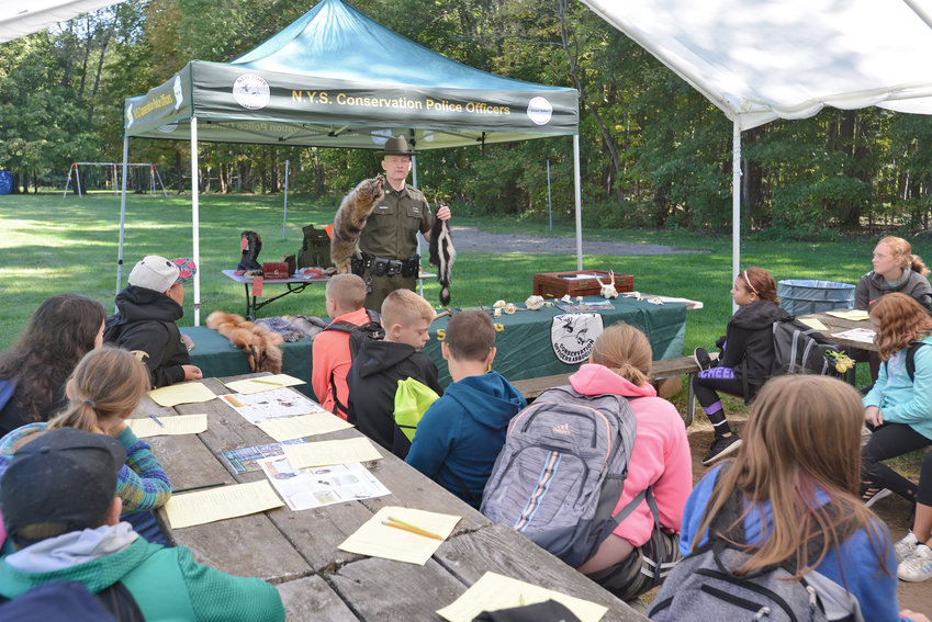 "PELTED WITH KNOWLEDGE — State Conservation Police Officer Ben Tabor shows a class of sixth-graders from Adirondack Middle School a variety of animal pelts at his Conservation Day station ""Sportsman Education and Hunter Safety"" on Tuesday at Delta Lake State Park. Dozens of classes from across the region attended the annual event designed to help children learn about the environment of upstate New York."
