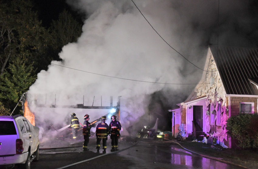 GARAGE LOST — Fire crews work to douse a fully involved garage fire at 8010 W. Thomas St., in the city's northern outer district. Authorities said no one was injured. The nearby residence sustained severe damage to the outside wall.