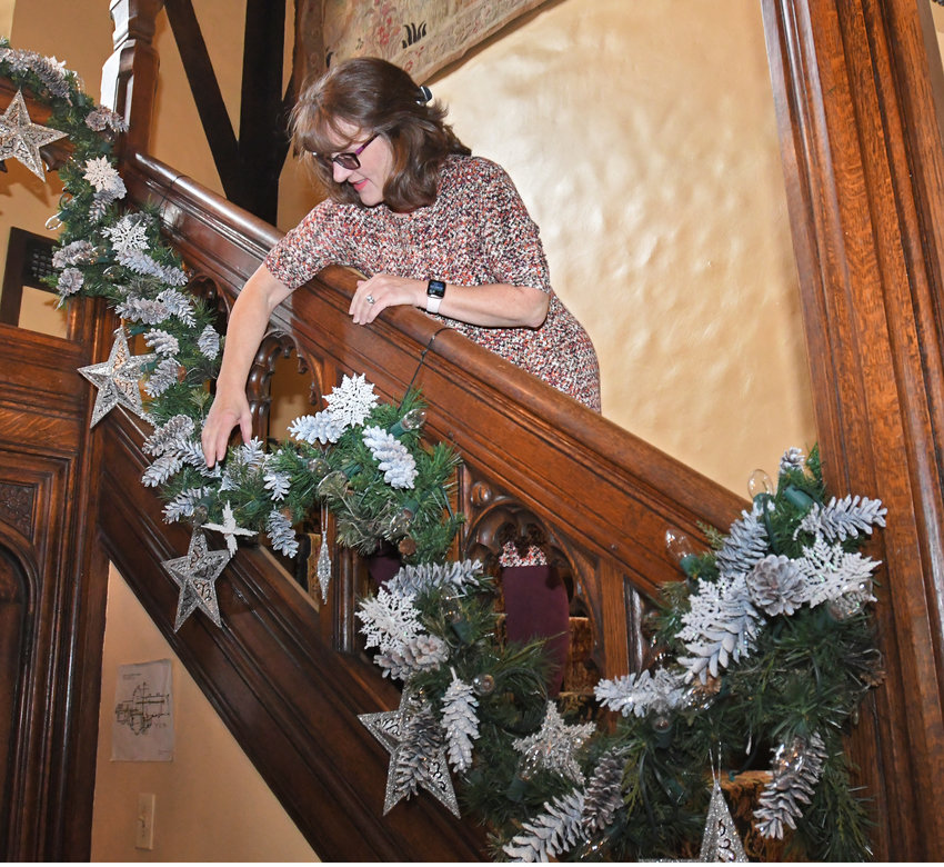 DECK THE HALLS — Tamalin Martin arranges garland on the stair case of the Rome Art and Community Center Wednesday morning in preparation of the 32nd Annual Holiday House event Nov. 16-17, and 22-24.