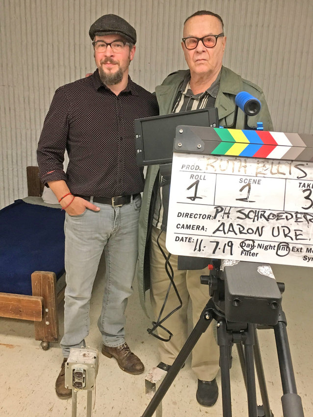 """COLLABORATORS — Aaron Ure, videographer, and producer/director Peter-Henry Schroeder pose for a photo inside a room at Oneida Municipal Center they are using to shoot the feature film, """"Ruth Ellis."""""""