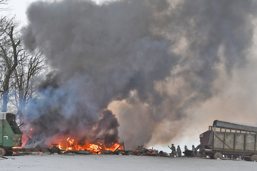 BARN BURNER — Thick black smoke billows into the air while an old storage barn burns to the ground on Old Oneida Road in Westmoreland this morning. Fire officials said no one was injured. Some chickens are believed to have gotten out in time. See story, additional photos, page 2.