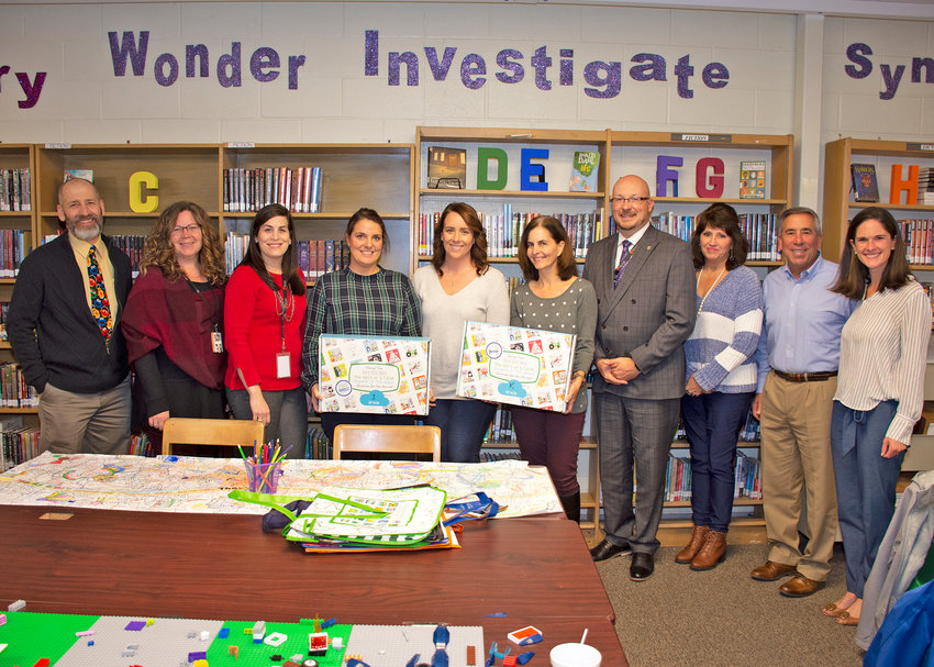 """WELCOMING 'ABC's OF STEM' — Rome school district representatives mark the donation of over 75 """"The ABC'S of STEM"""" kits for grades K-2, joined by officials from """"The ABC's of STEM"""" program and from local employers that funded the kits. From left: Jeffrey DeMatteis of the Rome Air Force Research Laboratory; Gansevoort Elementary School teacher Laurie Jones; school district Director of Fine Arts and and Engineering Technology Andrea Falvo; Staley Elementary School teachers Dixie White, Halley Bottini, and Julie Humphrey; district Superintendent Peter C. Blake; Bartell Machinery Systems Regional Human Resources Manager Pamela Hollenbeck; Bartell President Patrick Morocco; """"The ABC's of STEM"""" founder Karyn Burns-Gerling. STEM refers to science, technology, engineering, math."""