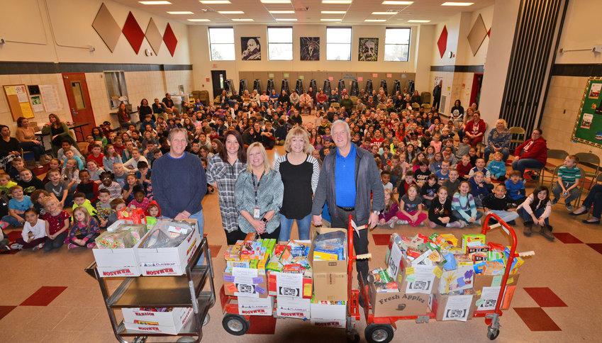 DENTI DONATIONS — Carts full of food items donated by Denti Elementary School students and staff are presented for Immanuel Baptist Church and the Rescue Mission of Rome this morning during a Giving Thanks assembly at the school. With the carts, from left: Matthew Miller, Rescue Mission executive director, and Destiny Branfalt, Rescue Mission administrative assistant; Denti Principal Sherry Lubey; Eileen Banks and her husband Ian Banks of Immanuel Baptist Church, where Ian is the pastor.