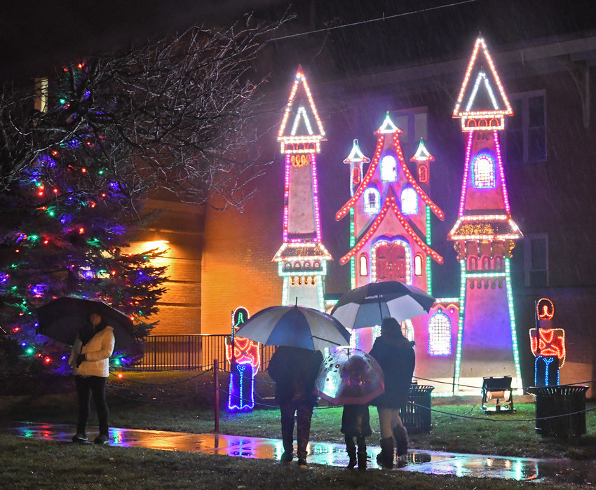 CITY LIGHTS  — A family enjoys the lit Trinkaus Village ornament in front of the Justice Building in Rome on Wednesday.