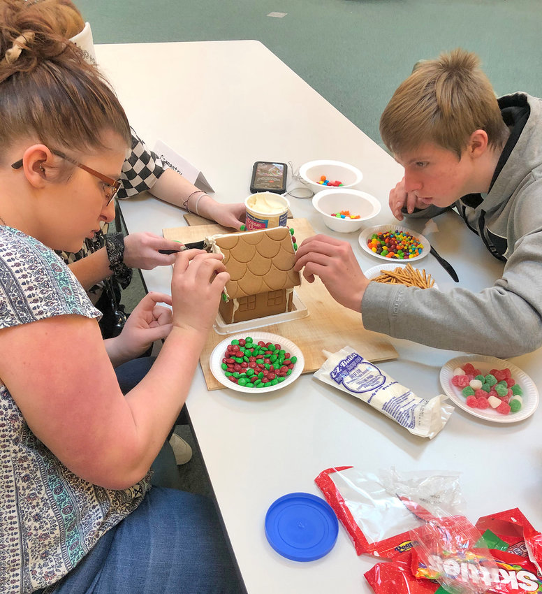 BOCES HOUSE CONTEST — From left, Madison-Oneida (MO) BOCES carpentry student Brianna Perry, culinary arts student Rebekah Conley, and carpentry student Shaun Willliams, all from the Vernon-Verona-Sherrill school district, participate in the first Rossetti Gingerbread House Challenge. Culinary arts students at MOBOCES made gingerbread cookie houses and invited student teams from BOCES Career and Technical Education classes to a decorating contest. Each team received frosting and some candy, but many also brought their own candy and decorations for their creations, said BOCES.