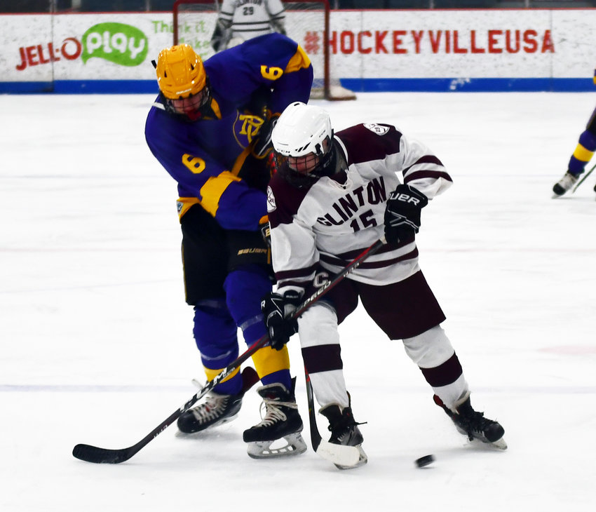BATTLE FOR THE PUCK — Clinton forward Derrick Jewel, right, and Christian Brothers Academy forward Ty Parker fight for control of the puck during the non-league contest on Friday, Dec. 20 at the Clinton Arena. The Warriors won, 3-0.