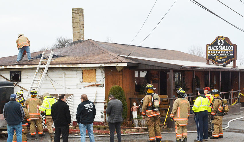 REKINDLED —Firefighters and insurance agents look on as a small rekindle is doused in the attic at The Black Stallion restaurant this morning. Fire officials said a wiring issue during renovations on Thursday sparked a blaze Thursday night, causing heavy damage in the ceiling and attic. The restaurant was closed for the month.