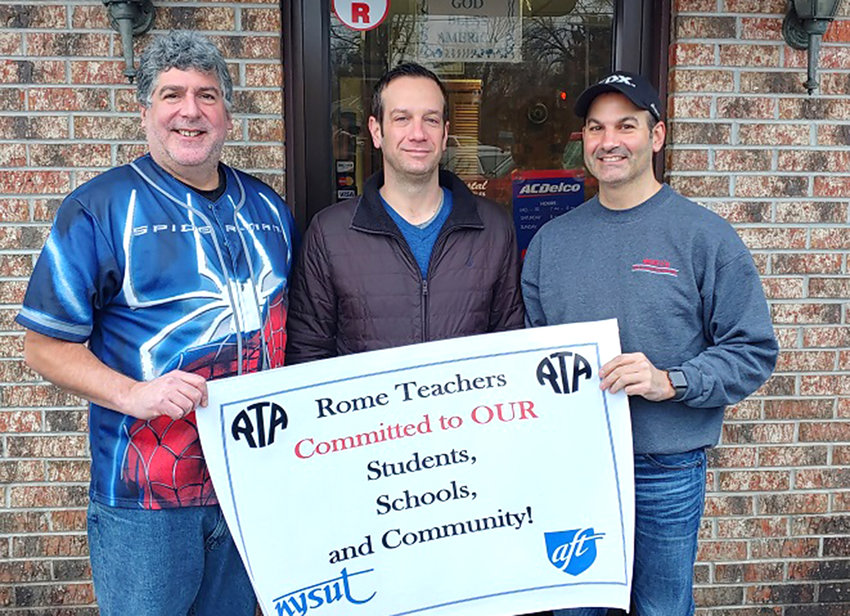 RTA RAFFLE FUNDRAISER —The Rome Teachers Association's annual community raffle fundraiser included drawings for prizes donated by local businesses. RTA President and community raffle chairperson Robert Wood, at left, and Ricky's Tire and Auto owner Ricky Cianfrocco, at right, congratulate Rome teacher Bryan Hand, at center, who won the raffle drawing grand prize which which included an installed car starter and winterizing auto kit.