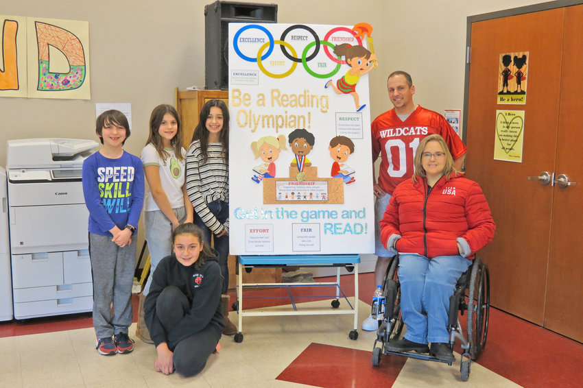 "ALUMNA HELPS LAUNCH CHALLENGE — Paralympic athlete and former Ridge Mills Elementary School student Tammy Delano, in front at right, was at the school to help a launch a ""Go for the Gold"" reading challenge for students. School Principal Michael Flagg is in back at right."