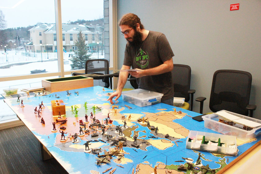 AXIS AND ALLIES — Michael Azzolino, president of the Morrisville Tabletop Gaming club and sophmore at SUNY Morrisville, sets up a replica of the 50th anniversary edition of the Axis and Allies board game, created by a friend of Associate Professor Richard Marcoux, to be played during the Global Game Jam at SUNY Morrisville.