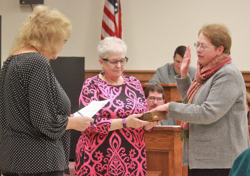 SWORN IN — Connie Coulthart, right, is sworn in by City Clerk Sue Pulverenti, left, as the Oneida city historian as Mayor Helen Acker holds Ward 3 Councilor, and Connie's husband, Jim Coulthart's family bible, during Tuesday night's Common Council meeting in City Hall.